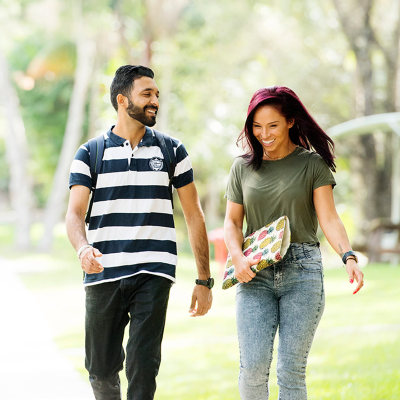 male and female students walking, smiling in outside setting at Lismore campus