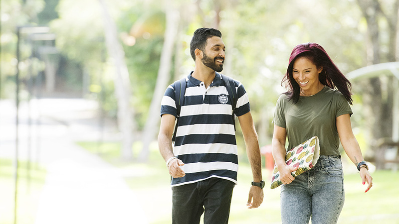 Male and female International students walking happily on campus