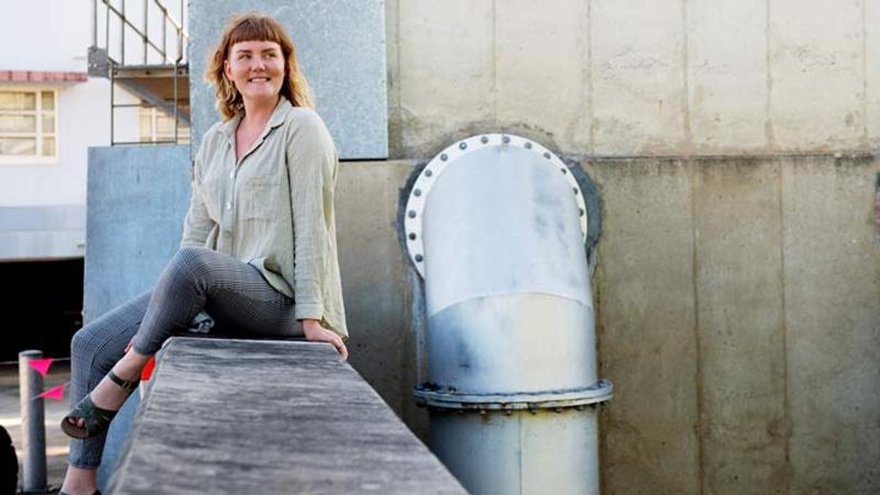 Woman sitting on concrete ledge