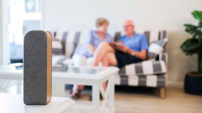 Smart device in foreground with blurred elderly couple in background