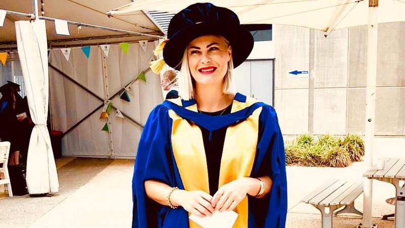 Smiling lady dressed in graduation attire