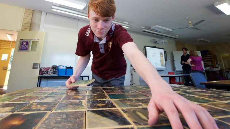 Young male school student participating in a project