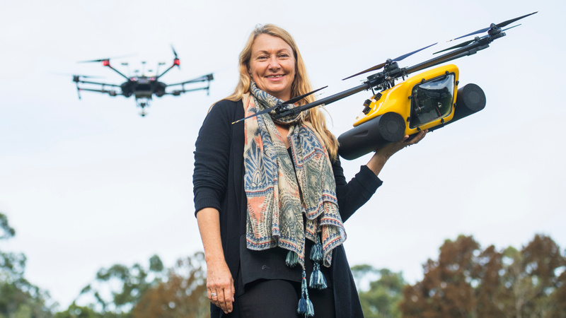 Women holding a drone used for research, with a drone flying in background
