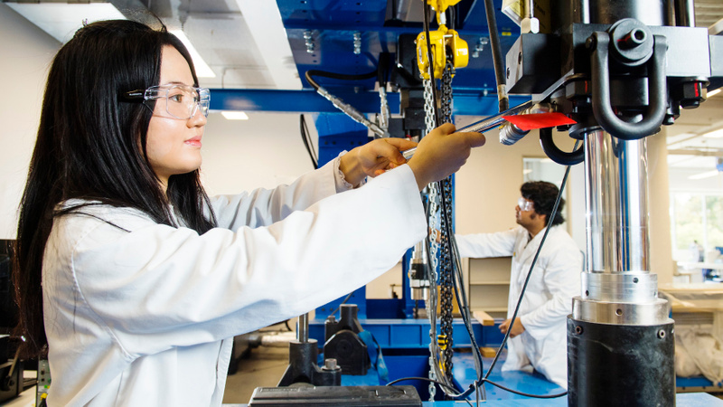 Female research student in lab coat working with mechanical engineering equipment