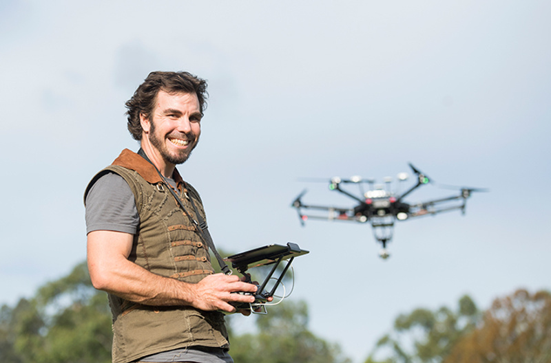 man standing with drone in flight