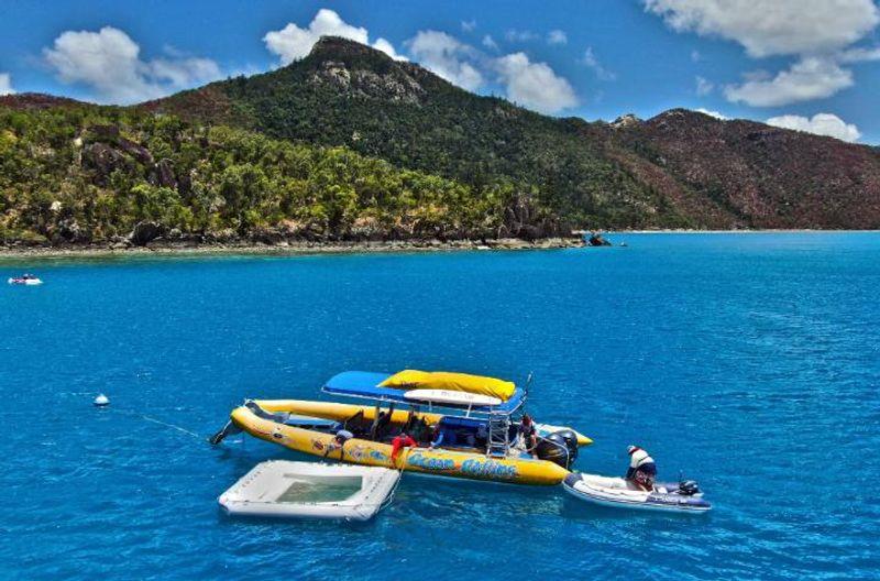 Boat in the ocean towing a coral larvae nursery pool