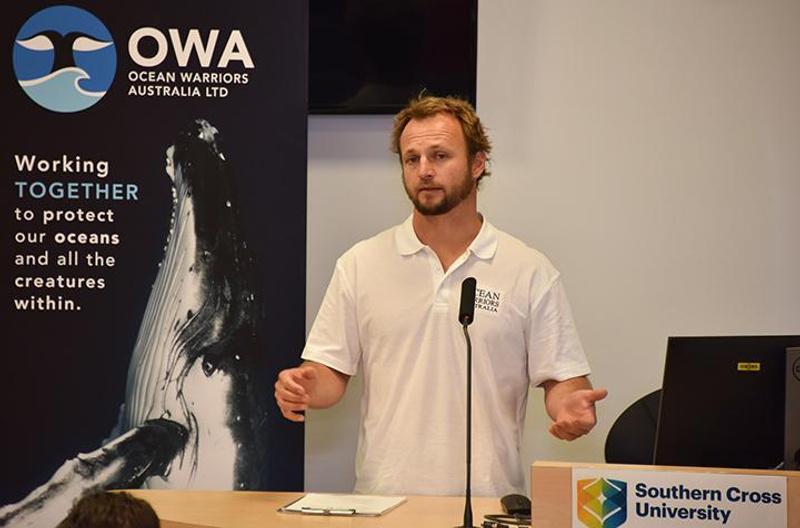 Man in white polo shirt making a presentation