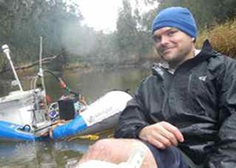 Male scientist on dinghy in river smiling at camera