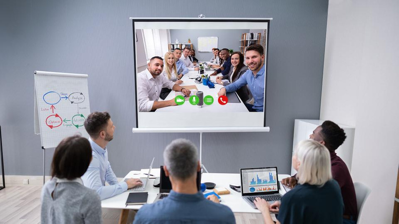 group of people meeting in person and online