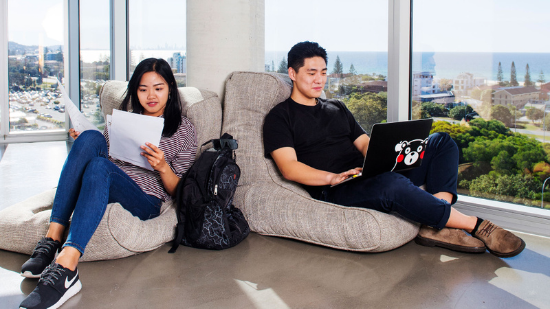 Two students studying with beach in the background