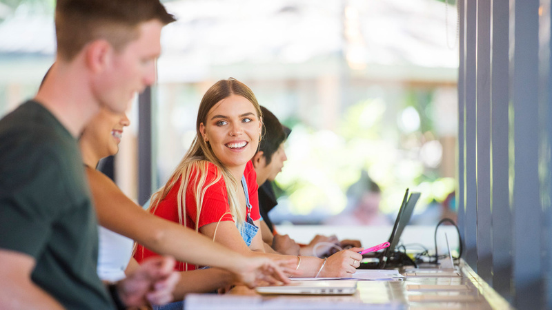 Female student smiling at friend while studying at the Lismore campus