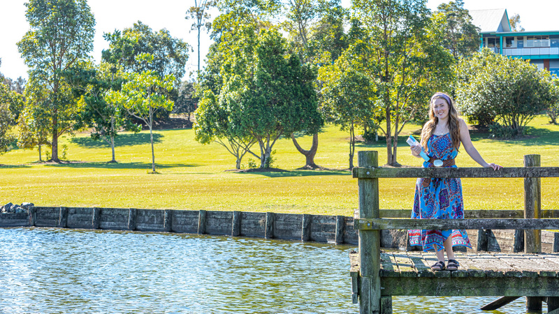 Female student by a lake at the Coffs Harbour campus