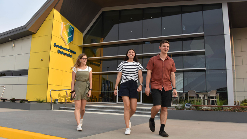 Three students walking in front of the Health Sciences building at Coffs Harbour
