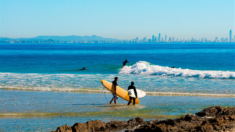 Surfers entering water with Gold Coast skyline in background