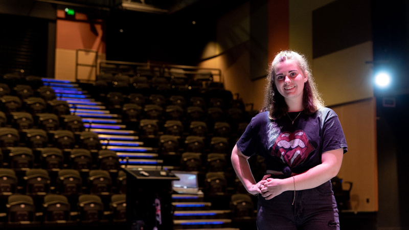 Female student smiling while standing in auditorium at Coomera campus