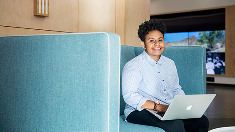 Student sitting on couch with laptop smiling
